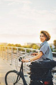 Transplant-Wissen > Informiert bleiben > Lebertransplantation > Frau gluecklich auf dem Fahrrad > Sonnenuntergang im Hintergrund